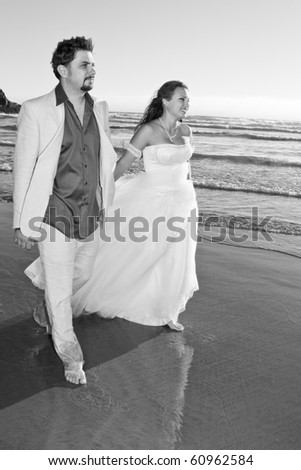 Happy bride and groom walking - stock photo