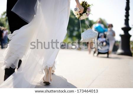 Happy bride and groom walking across the street - stock photo