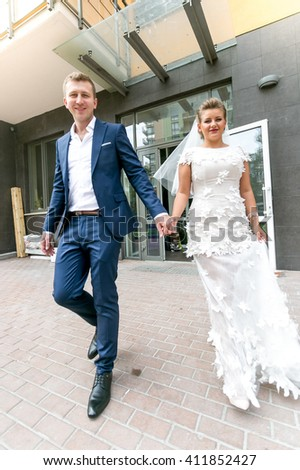 Happy bride and groom walking on street and holding hands - stock photo