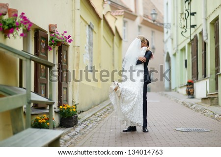Happy bride and groom walking together - stock photo