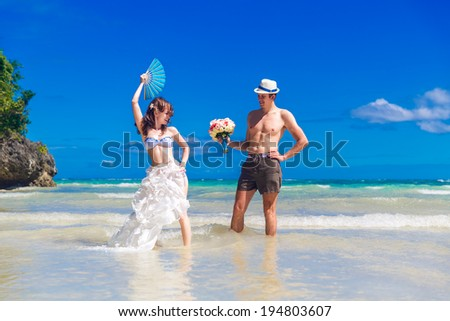 Happy bride and groom with a fan and a wedding bouquet having fun on the beach on the tropical island. - stock photo