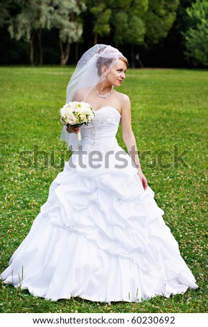 Happy bride at a wedding a walk in the park - stock photo