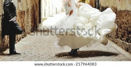 Happy bride dancing around boys. Wedding day  - stock photo