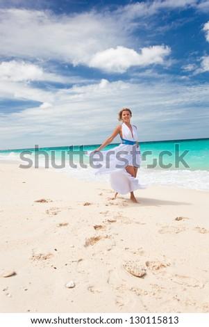 Happy bride in wedding dress  dancing on beach - stock photo