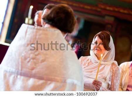 Happy bride is listening to priest during orthodox wedding ceremony - stock photo