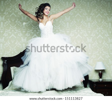 happy bride jump on bed. - stock photo