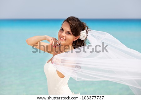 happy bride on a background of blue water of ocean. She is in her snow-white dress and veil flutters in the wind - stock photo