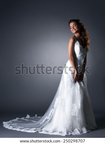 Happy bride posing in elegant wedding dress - stock photo