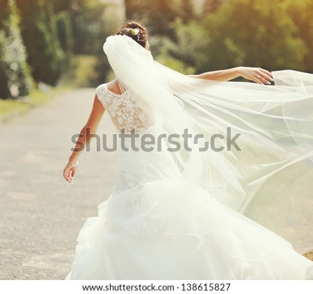 happy bride spinning around with veil - stock photo