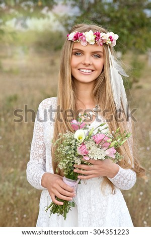 Happy bride with bouquet and flower wreath on sunset outdoor. Boho style. Series - stock photo