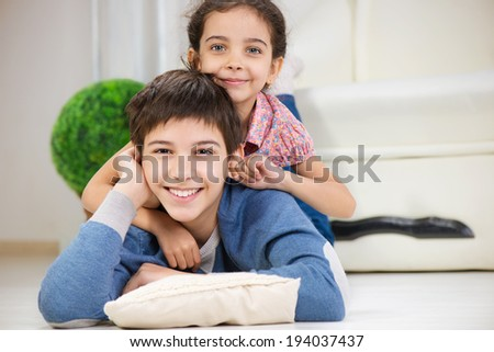 Happy brother and cute little sister at home - stock photo