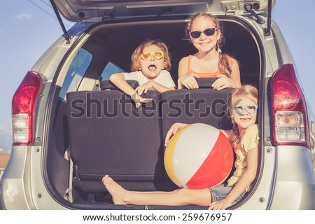 Happy brother and his two sisters are sitting in the car at the day time - stock photo