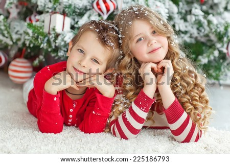 Happy brother and sister are playing on the floor near Christmas tree.  - stock photo