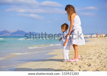 Happy brother and sister kids playing on tropical beach - stock photo
