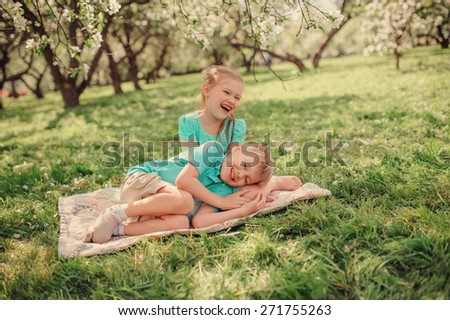 happy brother and sister playing and having fun in spring apple garden - stock photo