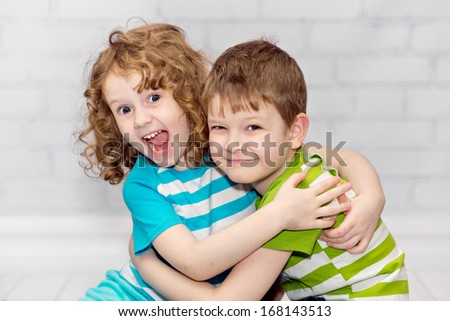 Happy brother and sister smiling and embracing. - stock photo