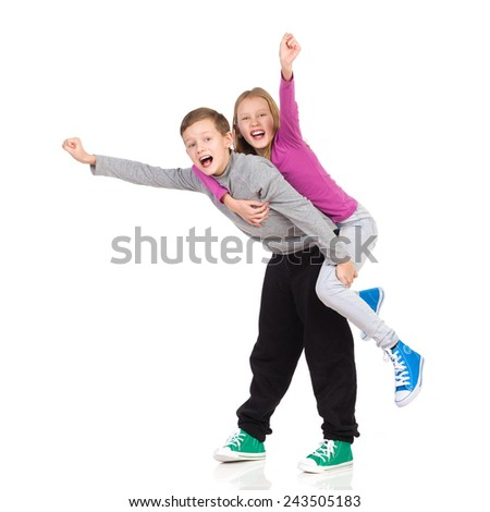 Happy brother and sister. Smiling boy carrying his sister on his back with their hands outstretched. Full length studio shot isolated on white. - stock photo