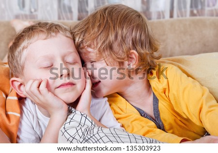 Happy brother and sister wake up in morning bed - stock photo