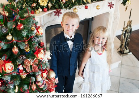 Happy brother sister holding hands near the Christmas tree and fireplace. children in evening dresses celebrate New year - stock photo
