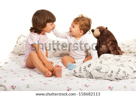 Happy brothers in bed standing together against white background - stock photo