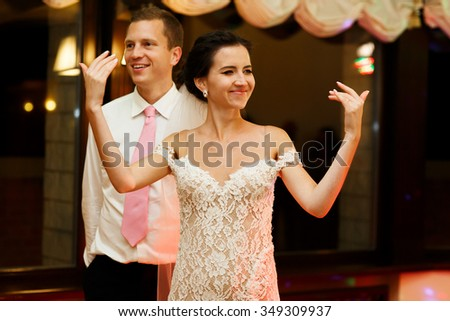 Happy brunette bride in vintage white dress and handsome groom dancing at wedding reception - stock photo