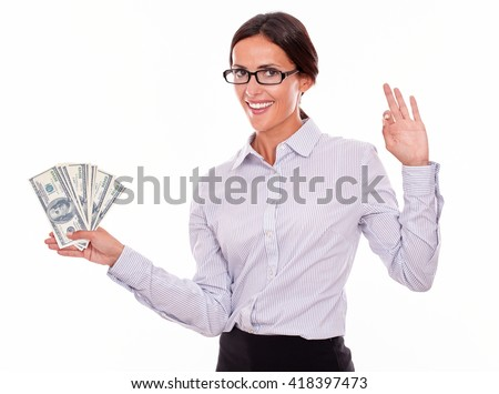 Happy brunette businesswoman holding dollar bills making a perfect gesture and smilingly looking at the camera while wearing a button down shirt and her hair tied back on a white background - stock photo