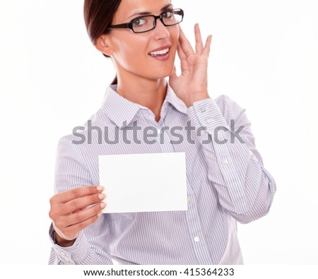 Happy brunette businesswoman with glasses, toothy smile, wearing her long hair tied back, and a button down shirt, holding a blank copy space in one hand gesturing her surprise with the other hand - stock photo