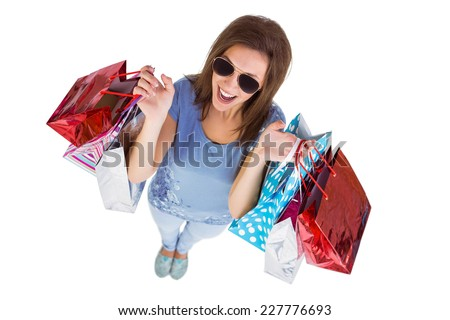 Happy brunette holding shopping bags on white background - stock photo