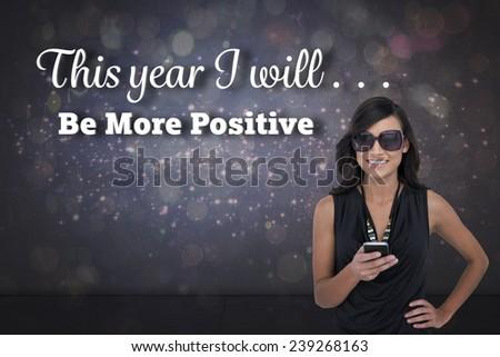 Happy brunette holding smartphone against purple glittering light on black - stock photo