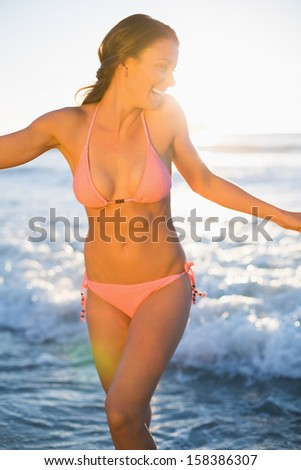 Happy brunette in pink bikini on the beach at dusk - stock photo