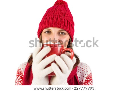 Happy brunette in winter clothes holding mug on white background - stock photo