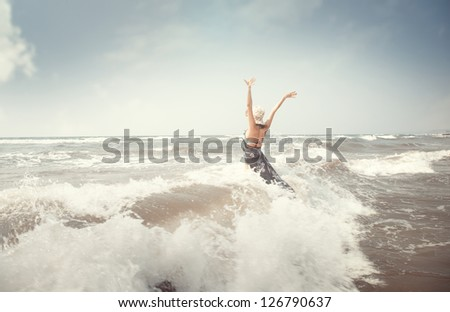 Happy brunette lady in the sea playing with waves - stock photo