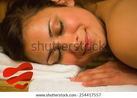 Happy brunette lying in a sauna against heart - stock photo