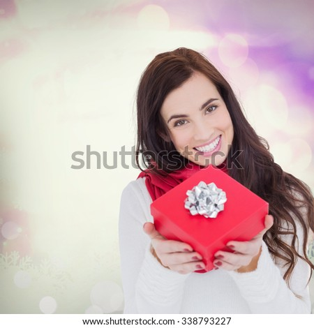 Happy brunette showing red gift with a bow against glowing christmas background - stock photo