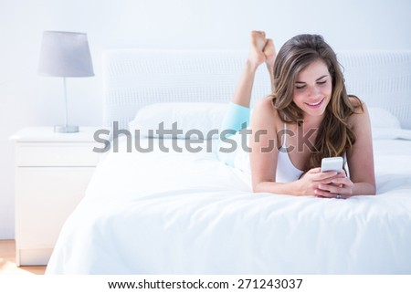 Happy brunette using her smartphone in her bed at home in the bedroom - stock photo