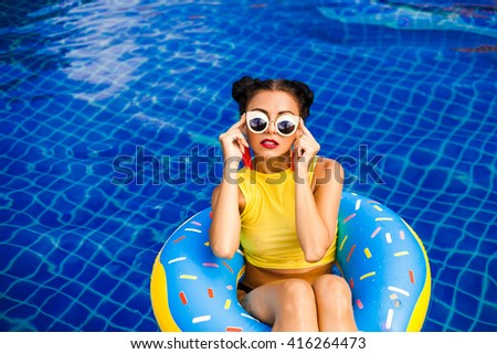 Happy Brunette Woman in sunglasses. Beauty girl with bright makeup hairstyle with horns in a sexy bikini swims on an inflatable circle, stylish, fashionable accessories, hipster, luxurious style - stock photo