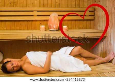 Happy brunette woman lying in a sauna against heart - stock photo