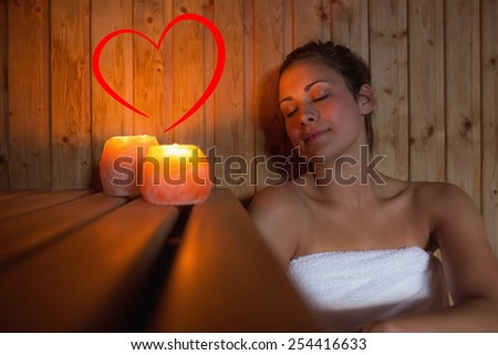 Happy brunette woman sitting in a sauna against heart - stock photo