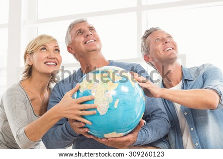 Happy business colleagues holding terrestrial globe and looking above - stock photo