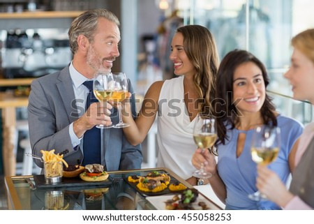 Happy business colleagues interacting and toasting beer glasses while having lunch in a restaurant - stock photo