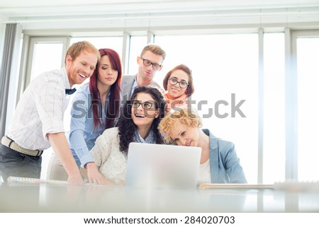 Happy business colleagues with laptop discussing in creative office - stock photo