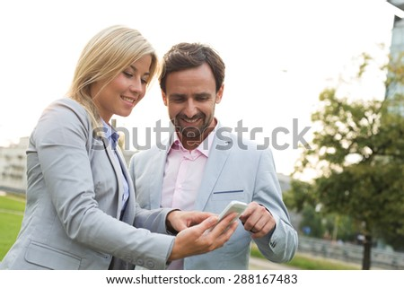 Happy business couple using smart phone at park - stock photo