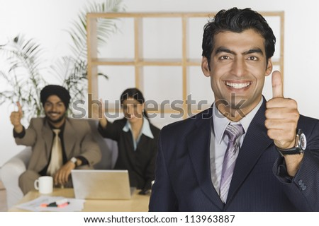 Happy business executives showing thumbs up sign - stock photo
