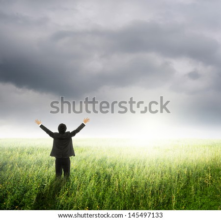 Happy business man in green fields and rainclouds - stock photo