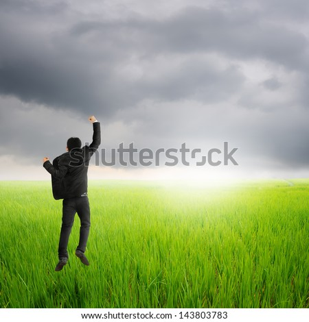 Happy business man jumping in green rice field and rainclouds - stock photo