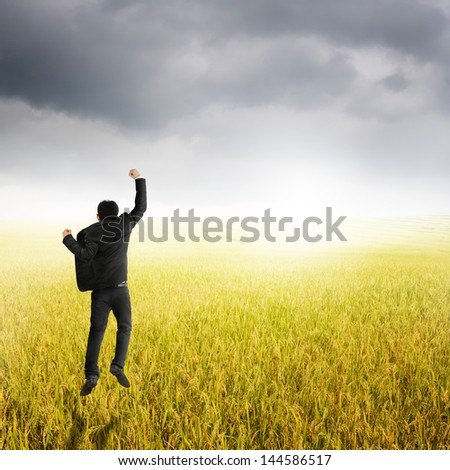 Happy business man jumping in yellow rice field and rainclouds - stock photo