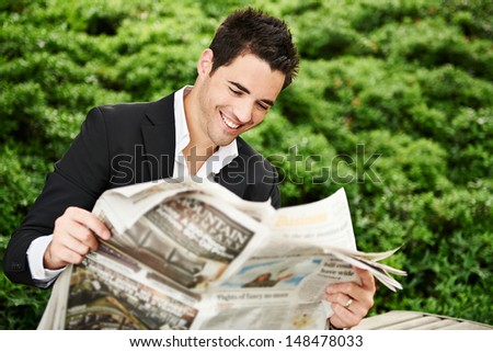 Happy business man reading a newspaper - stock photo