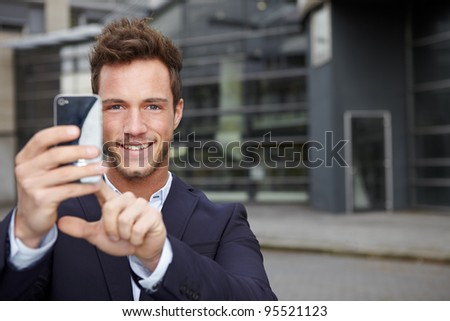 Happy business man taking pictures with smartphone in city - stock photo