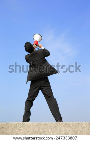 happy business man using megaphone shouting with blue sky background, asian - stock photo