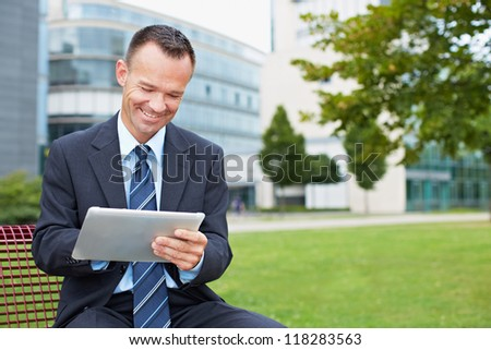 Happy business man using tablet PC outside on a park bench - stock photo